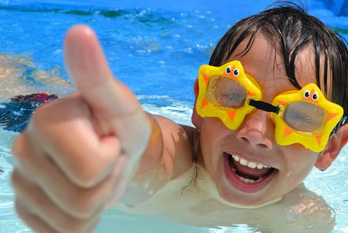 Ein lachender Junge mit Taucherbrille hebt im Schwimmbad seinen Daumen in die Luft.