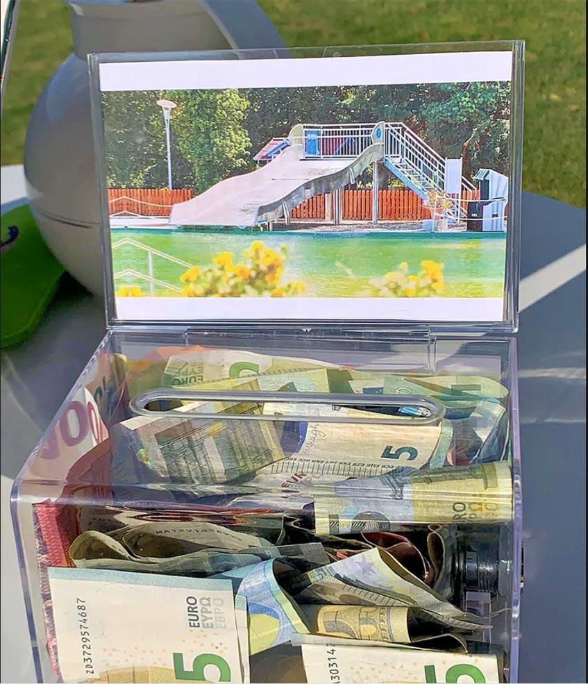 Gefüllte Spendenbox mit Foto einer Breitwasserrutsche
